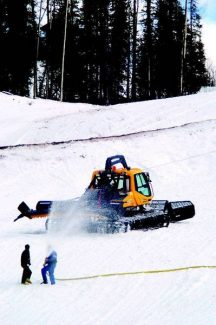 Workers spray down the Spring Pitch run as a snowcat moves snow around Wednesday. The run is part of the giant slalom course for the women's World Cup races on Thanksgiving weekend. Aspen Times photo/Mark Fox.