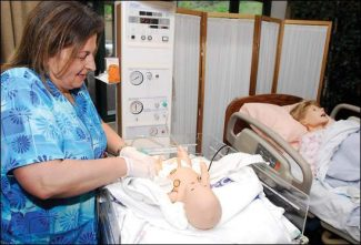 Valley View Hospital nurse Jane Vincent demonstrates a birthing simulator designed to replicate a variety of birthing scenarios. The simulator is used as a training tool for hospital staff. (Chad Spangler/Post Independent)