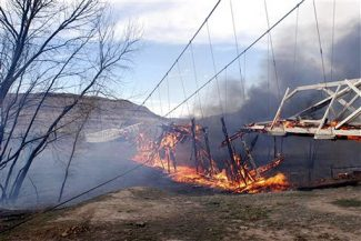 In this photo released by the Grand County Sheriff Department, the historic Dewey Bridge burns Sunday, April 6, 2007, near Moab, Utah.  The 92-year-old wooden suspension bridge across the Colorado River caught fire when a boy playing with matches caused a brush fire. The bridge is on the National Register of Historic Places. (AP Photo/Grand County Sheriff Dept., HO)  ** NO SALES **