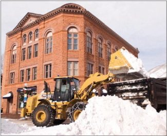 Paul Conrad/The Aspen TimesSteve Ross, Aspen parks department construction manager, unloads a bucket of snow into a dump truck this week in front of the Wheeler Opera House. Snow has fallen every day since Sunday in Aspen, keeping streets crews busy.