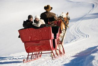 Mid-adult Caucasian couple taking a sleigh ride looking back at viewer.