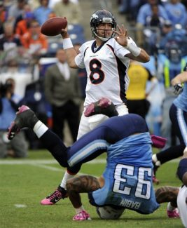 Denver Broncos quarterback Kyle Orton (8) passes as Tennessee Titans defensive end Jason Babin (93) is tripped in the fourth quarter of an NFL football game on Sunday, Oct. 3, 2010, in Nashville, Tenn. (AP Photo/Frederick Breedon)