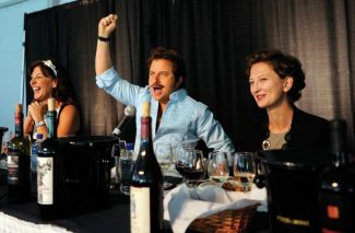 Mark Oldman exhorts the crowd to vote for his pairing of food and wine as Laura DePasquale (left) and Vilma Mazaite laugh along during the Iron Sommelier event on Friday morning in Paepcke Park. (Patrick Ghidossi/The Aspen Times)