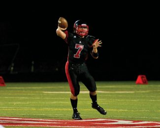 Freshman quarterback Tucker Beirne looks to pass downfield during the first half of the Aspen Skiers' victory over the visiting Delta Panthers at Aspen High School Friday night. (Patrick Ghidossi/The Aspen Times)