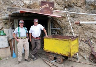 Jay Parker, left, and Chris Preusch, two of the now-former owners of the Smuggler Mine, stand at one of the silver mine's portals, where tours exit the mountain, in 2012.