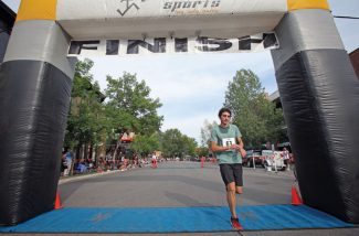 Ryan Slabaugh/The Aspen TimesCarlos Ruibal crosses the finish line to win Wednesday's Boogie's Diner Buddy 5 Mile Race in downtown Aspen. Ruibal, 25, completed the course in 28 minutes, 42 seconds - nearly 2 1/2 minutes ahead of his nearest competitor.