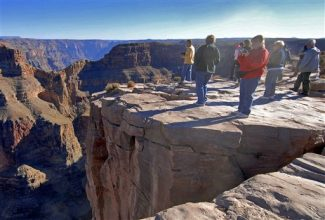 FILE - In this Dec. 7, 2006 file photo, tourists visit the Hualapai Indian Reservation along the western end of the Grand Canyon. A new study published in the journal Science Thursday, Nov. 29, 2012, suggests the western Grand Canyon formed 70 million years ago.  Some scientists disagree and believe the canyon was mainly carved by the Colorado River in the past 5 to 6 million years. (AP Photo/Jake Bacon, File)