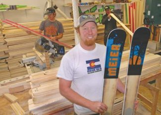 Kelley Cox/Post IndependentMatt Cudmore displays a pair of Meier skis at the company's new production headquarters south of Glenwood Springs. Full-time production workmen Chris Dean, left, and Chris Kennedy are shown in back.