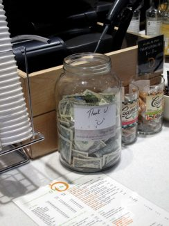 Andre Salvail/The Aspen TimesA tip jar half-filled with one-dollar bills sits on the counter at Peaches Corner Cafe at the corner of South Galena Street and East Hopkins Avenue. Aspen coffee shops and quick-food establishments generally encourage customers to provide a gratuity, given that service is provided in a manner similar to restaurants and bars.