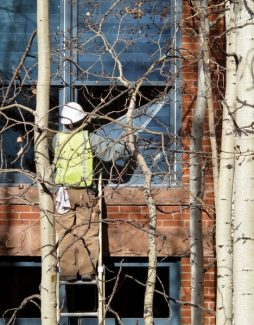 """Andre Salvail/The Aspen TimesA construction worker peels the plastic covering off of the new energy-efficient windows at the Hotel Jerome on Monday. The hotel will hold its """"soft"""" re-opening on Dec. 14, including the J-Bar."""