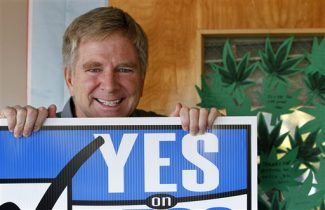 """ADVANCE FOR USE MONDAY, DEC. 3, 2012 AND THEREAFTER - In this Monday, Nov. 26, 2012 photo, travel guide author and marijuana legalization supporter Rick Steves holds a campaign sign in his office in Edmonds, Wash next to a door covered with marijuana leaf-shaped notes from his staff congratulating him on the passage of a referendum legalizing marijuana in the state. In the late-1980s heyday of the """"Just Say No"""" campaign, a man calling himself """"Jerry"""" appeared on a Seattle radio station's midday talk show, using a pseudonym because he was a businessman, afraid of what his customers would think if they heard him criticizing U.S. marijuana laws. A quarter century later, """"Jerry"""" had no problem using his real name - Rick Steves - as one of the main forces behind Washington's successful ballot measure to legalize, regulate and tax marijuana for adults over 21. (AP Photo/Elaine Thompson)"""