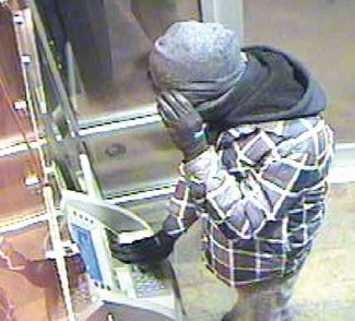 """Courtesy of the Aspen Police DepartmentA suspect in a recent case in which an Aspen bank's ATM machine was rigged with a """"skimmer"""" device shields his face from a security camera."""