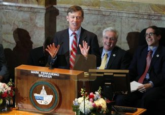 Colorado Gov. John Hickenlooper, front, makes a point during his annual State of The State speech before a joint session of the Colorado Legislature in the State Capitol in Denver on Thursay, Jan. 10, 2013. Looking on are Senate President John Morse, D-Colorado Springs, back left, and Speaker of the House Mark Ferrandino, D-Denver. (AP Photo/David Zalubowski)