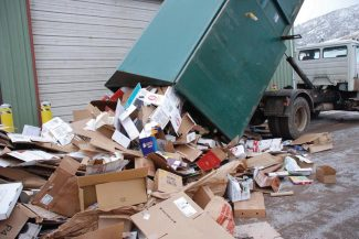 A container of cardboard spills onto a pile at the Pitkin County Solid Waste Center in this 2013 file photo.