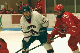 Leah MoriartyAspen High senior Gus Gregory battles a Regis Jesuit player for the puck Saturday at Lewis Ice Arena. Aspen won, 4-2.