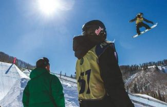 Justin McCarty/Vail DailyCompetitor Stefi Luxton, center, and Method Snowboard Academy coach Cameron Hunter, left, watch as athletes fly over the second booter of the slopestyle course on the first day of training for the Burton U.S. Open Snowboarding Champions Monday in Vail.