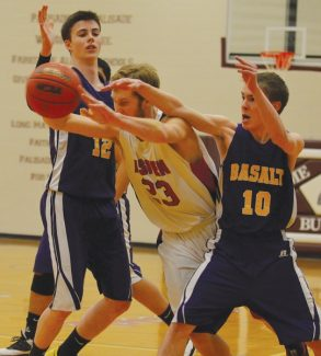 Aspen High School's Trent Lichtenwalter (center) wedges his way between Basalt's Spencer Glasener (12) and Patrick Reynolds (10) in the first quarter of the third-place game of the Class 3A Western Slope League District Tournament on Saturday in Palisade.