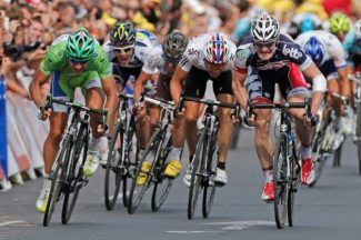 Stage winner Andre Greipel of Germany, right in blue, Peter Sagan of Slovakia, wearing the best sprinter's green jersey, left, and Edvald Boasson Hagen of Norway, second right, sprint towards the finish line to win the 13th stage of the Tour de France cycling race over 217 kilometers (134.8 miles) with start in Saint-Paul-Trois-Chateaux and finish in Le Cap D'Agde, France, Saturday July 14, 2012. (AP Photo/Laurent Rebours)