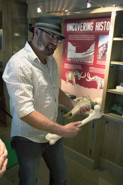 Paleontologist Tom Temme compares the femur of a bison to a human's in the Ice Age Discovery Center.