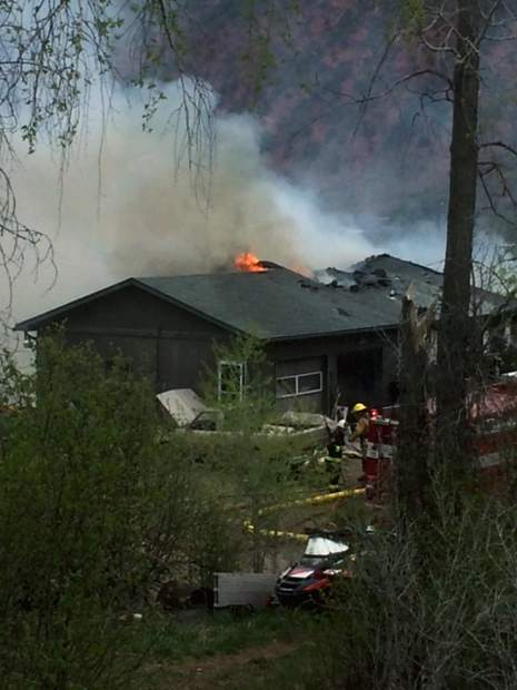 Dying flames poke through the roof of the home destroyed by fire Monday.