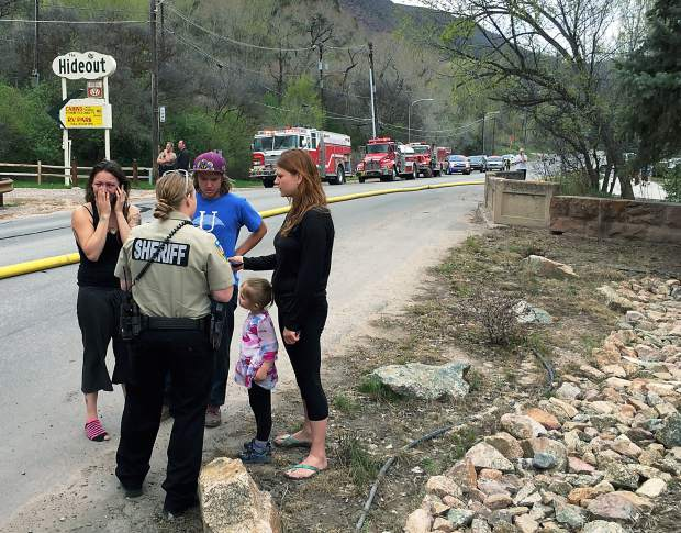 An unidentified woman at left talks on her cell phone while authorities interview others near the scene of Monday afternoon's fire in south Glenwood Springs.