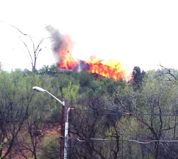 Flames rise Monday afternoon from a home in south Glenwood Springs.