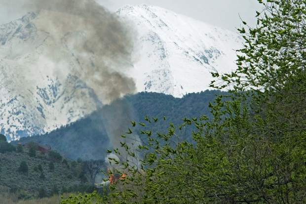 Smoke from Monday's fire rises against Mount Sopris' snowpack.