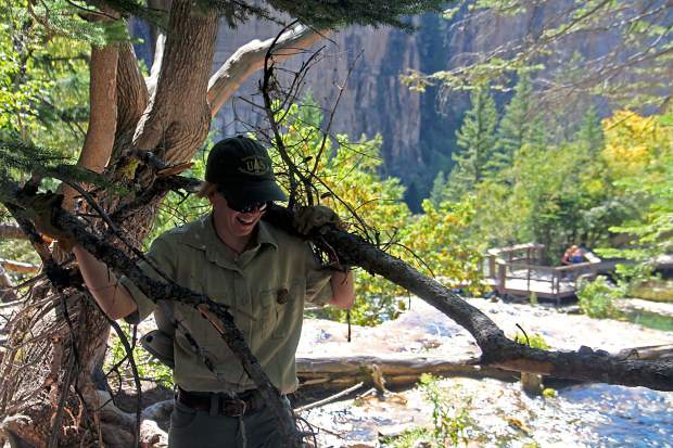 Ranger Kelsey King gathers wood to block paths above Hanging Lake during a trail workday.