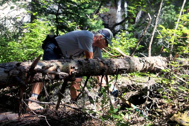 Roaring Fork Outdoor Volunteers member Lee Smith covers up a social trail just below Spouting Rock.