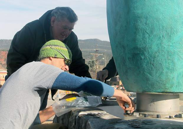 James Surls (back) supervises as his sculpture is bolted into place.