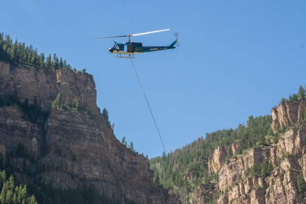 A helicopter works to fly rockfall fencing into place in Glenwood Canyon on July 27.