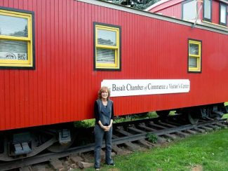 Robin Waters, the new executive director of the Basalt Chamber of Commerce, stands outside the organization's signature red caboose at Lions Park.