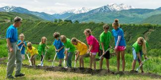 "Students of the Aspen Community School break ground on their redesigned campus in Woody Creek last summer while principal Jim Gilchrist (left in blue shirt) looks on. The K-8 public charter school is currently considering dropping ""Aspen"" from its name."