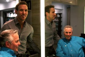 Marc Ostrofsky, seated, looks into a mirror at the Salon Myo Aspen with his third cousin, Joshua Rossignol. The two men met at the Aspen-Pitkin County Airport and two months later came to realize they were related.