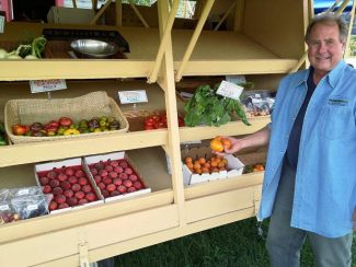 Skip Doty, owner of Early Morning Orchard, displays some of the produce from his stand. Construction at the base of Buttermilk forced him to move his stand this summer to Cozy Point Ranch.