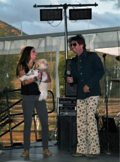 Seth Sachson, wearing his shades and disco bell bottom pants, auctions off Winnie the dog to the Seth Burger family from New York at the 2013 fundraiser. Sachson's sister, Jill Trattler, helps with the auction and is holding Winnie.