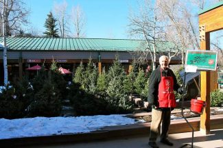 Darrell Morrow, a member of the Aspen Rotary Club, rings his bell for the Salvation Army Holiday Red Kettle program at the Christmas-tree lot outside Clark's Market. Last year, the Salvation Army raised $17,500.