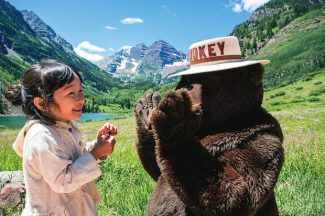 Tou Ikeda, 5, of Madison, Wis., visits with Smokey Bear on Saturday at Maroon Lake. She and her family, originally of Japan, celebrated Smokey Bear's 70th birthday at the Maroon Bells. Her father, Manabu Ikeda, is an artist.