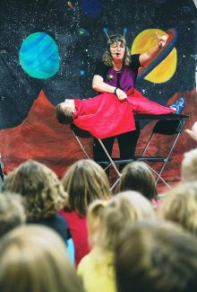 Entertainer Ann Lincoln levitates a volunteer from the audience in a make-believe bed on Mars. The Space Alien Big Bang Magic Show was held at the Pitkin County Library on Tuesday afternoon.