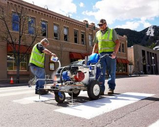 City worker Seth Collar pours glass beads into the fresh crosswalk paint being applied by Matt Wieben, at the intersection of Main Street and Mill Street on Thursday.