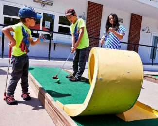 Mikel, 4, and Matias Hong, 8, from left, with their cousin Ava Gonzales, 10, play a round of miniature golf at the makeshift course, located at the Silver Circle Ice Rink in downtown Aspen. The course is open daily from 11 a.m. to 10 p.m.
