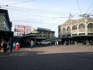 """Pictured is Seattle's Pike Place Market, with its multistory arcade spilling down the hillside offering many water-view dining options, including the Athenian Seafood lunchroom where scenes were filmed for  """"Sleepless in Seattle."""" The Corner Market, on the lower right, continues to expand the varieties of produce offered. The first Starbucks is just around the right corner facing the main market."""