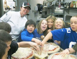 Aspen Elementary School students prepare pizza with chef Tenille Folk as part of her Cooking Club. Helping Folk is John Schille, Chloe Ferraro, Grace Peacock, Maya Hull and Lucas Lee in the football jersey.