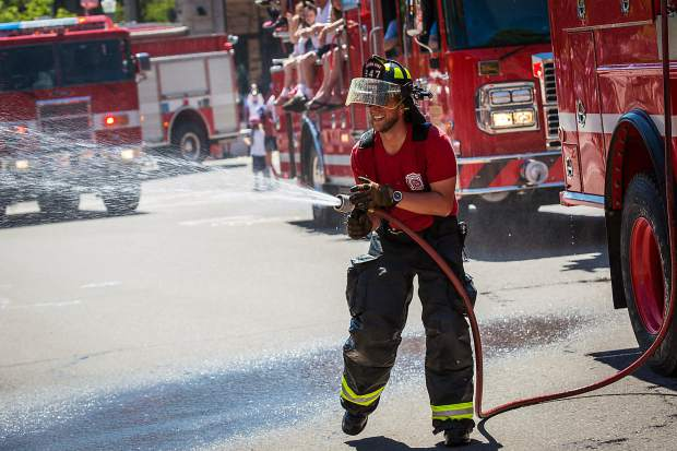 A firefighter sprays parade onlookers downtown Monday.