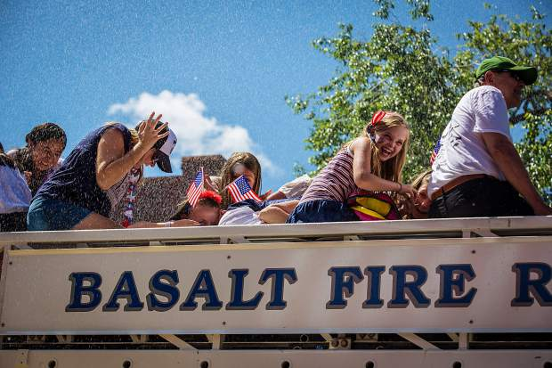 People riding the Basalt fire truck through the 4th of July parade in Aspen get sprayed by the Aspen Volunteer Fire Department.