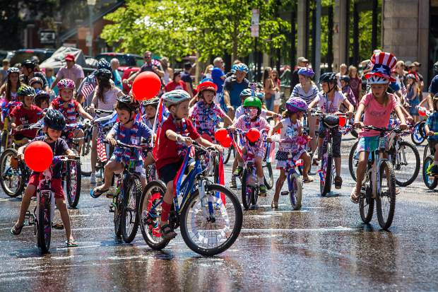 Dozens of kids on bikes ride through the streets of downtown Aspen Monday for the 4th of July parade.