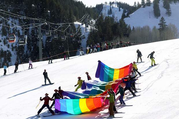 A massive gay pride flag is skied down the Little Nell run Friday afternoon during Aspen Gay Ski Week's Downhill Costume Contest.