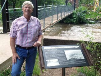 Bill Hegberg stands beside a Basalt History Tour sign near the swinging bridge. The tour features 12 signs strategically placed around the town to raise awareness of the town's history.