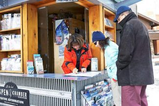 Sue Wall points visitors in the right direction at the Aspen Chamber Resort Association information kiosk Thursday.