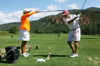 Golf professional Dede Cusimano, left, works on a drill with Tom Harbison at the Aspen Golf Club driving range Wednesday morning.